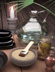 Spa still life with burning candle and clay mask on wooden background.