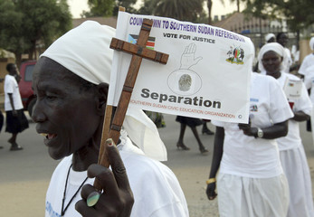 Southern Sudanese women hold crosses and flags to support the referendum on southern independence, during a Christmas Eve procession in Juba