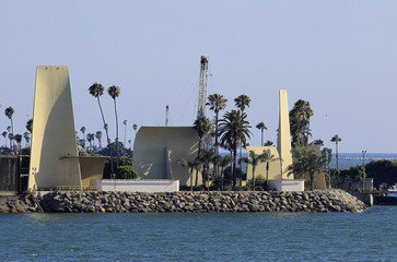 Temporary drill rig tower is seen among various structures and palm trees that are used to hide oil extraction operations on Island White
