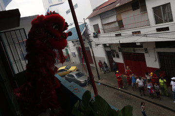 Dancers perform a lion dance on a balcony of the Yan Wo temple as locals look on during celebrations of the Chinese Lunar New Year of the Monkey in Chinatown in Panama City