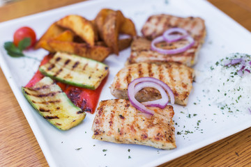 Grilled chicken with grilled vegetables on white plate.