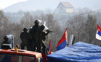 A Kosovo Force (KFOR) soldiers from Germany and Austria aims a riot gun towards Kosovo Serbs during clashes in the village of Jagnjenica near the town of Zubin Potok