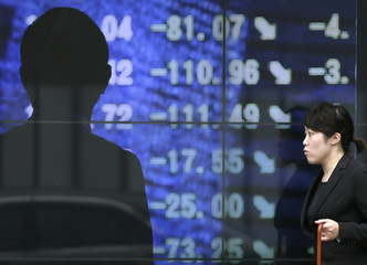 A woman walks past a markets index board showing a news photo of stock markets in Tokyo