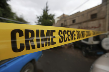 Police tape is seen at a crime scene where a French man was assassinated in a car, in Sanaa