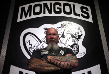Member of the Mongols Motorcycle Club, known only as 'Ozzie', poses