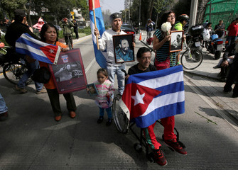 Supporters hold pictures of Fidel Castro and Cuban flags as they attend a tribute ceremony, following the announcement of the death of Cuban revolutionary leader Castro outside the Cuban Embassy, in Mexico City