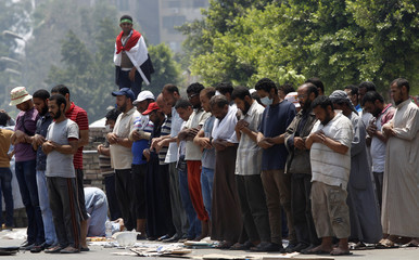 Members of the Muslim Brotherhood and supporters of Mursi pray at Republican Guard headquarters in Nasr City