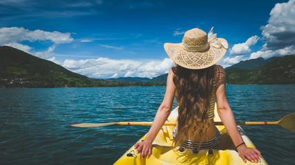 In de dag Ontspanning Young woman with hat and beautiful long hair relaxing in kayak on alpine lake