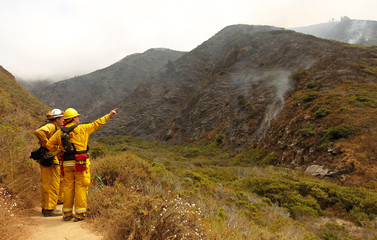 Firefighters from El Dorado Hills keep watch on a smoldering cliff at Garrapata State Park during the Soberanes Fire north of Big Sur, California