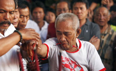 An ethnic Chinese man pierces his mouth with needles during the Cap Go Meh festival in Bogor, West Java