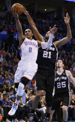 Oklahoma City Thunder guard Russell Westbrook shoots against San Antonio Spurs forward Tim Duncan and Nando De Colo of France, in the second half of their NBA basketball game in Oklahoma City.