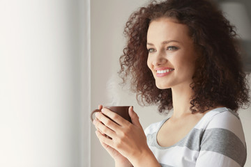 Young woman holding cup of coffee and looking at window
