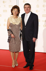 """German Olympic sports association (DOSB) President Bach and his wife pose on the red carpet as they arrive for the """"Sportsmen of the year"""" gala in Baden Baden"""
