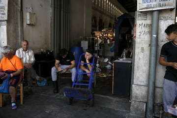 Youths working at Athens' main fish market rest at the entrance of the market