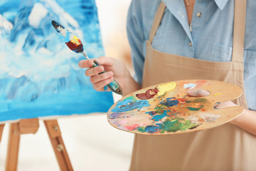 Female artist holding palette and spatula