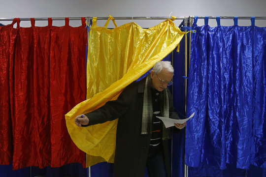 A man leaves a polling booth decorated with Romania's national flag colours at a voting station in Bucharest