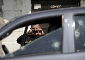 A police officer take pictures of a car with bullet holes where Luis Andres Cuyun, director of Las Gaviotas juvenile remand centre was murdered, in Guatemala City