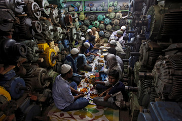 Muslims eat their iftar meal at a water pump workshop in the old quarters of Delhi