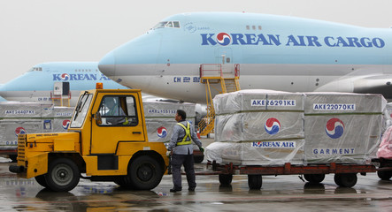 Korean Air workers transport pallets of cargo at the cargo terminal of Incheon International Airport