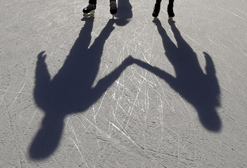 A couple casts shadows on the ice as they hold hands and skate on an outdoor rink in Millennium Park in Chicago, Illinois, United States