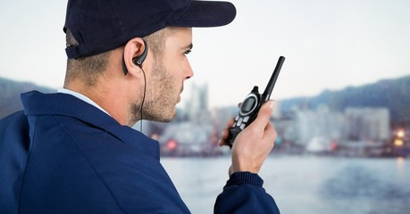 Security guard with cap and walkie talkie against blurry skyline