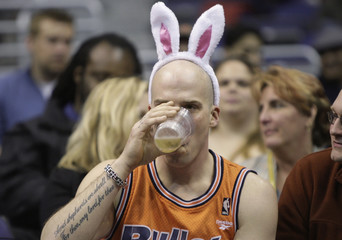 Wizards fan wearing bunny ears on Easter Sunday, drinks during NBA basketball game against the Toronto Raptors in Washington