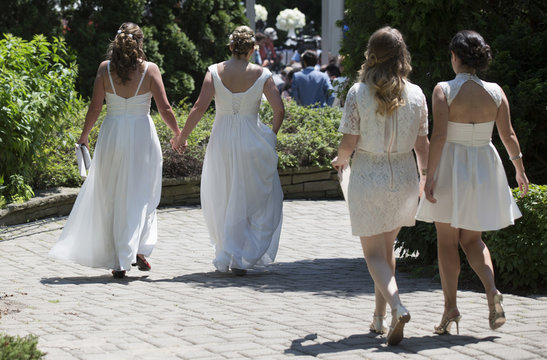 """Couples walk down a pathway to the """"The Celebration of Love"""", a grand wedding where over 100 LGBT couples will get married, at Casa Loma in Toronto"""