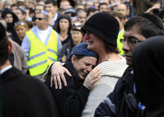 Mourners cry during the funeral of Ehud Fogel, his wife Ruth and their children in Jerusalem