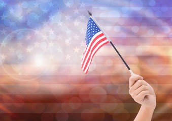 Hand with American flag with sparkling light bokeh background