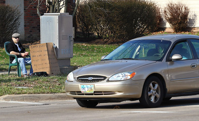 "Aviv sits with an ""I am a bully"" sign, as a car stops to take pictures, at a street corner in the Cleveland suburb of South Euclid"