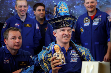 The International Space Station (ISS) crew member Jeff Williams of the U.S., wearing Kazakh national costume, holds a traditional Russian Matryoshka wooden doll depicting him at a news conference in Karaganda, Kazakhstan