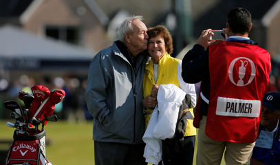 Palmer of the U.S. kisses his wife Kathleen Gawthrop as they pose for a photograph on the first green during the Champion Golfers' Challenge tournament ahead of the British Open golf championship on the Old Course in St. Andrews, Scotland