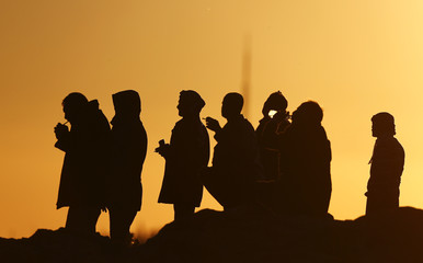 Turkish Kurds watch the Syrian town of Kobani from a hill near the Mursitpinar crossing, on the Turkish-Syrian border