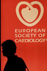 A participant walks past a poster bearing the symbol of a heart at the European Society of Cardiology meeting venue in Amsterdam