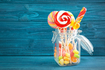 Wall Mural - Different candies in glass jar on wooden background