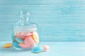 Jelly candies in glass jar on wooden background