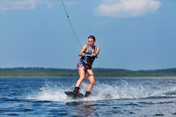 slim woman riding wakeboard on wave of boat