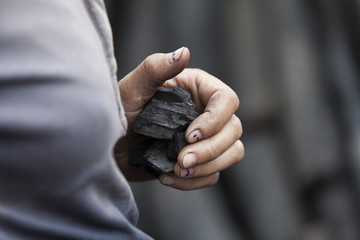 Closeup on hand with small piece of coal