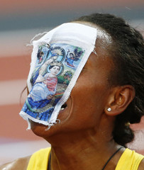 Ethiopia's Meseret Defar, with a piece of cloth with an image of a religious icon on her face, reacts after she won the women's 5000m final during the London 2012 Olympic Games