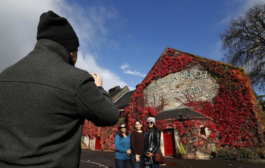 Tourists take photographs at the Blair Athol Distillery Pitlochry, Scotland
