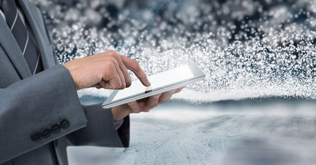 Businessman holding tablet with snow backgorund