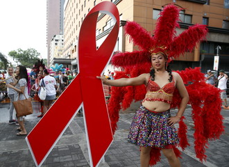 A Filipino transgender woman holds a huge red ribbon symbolizing fight against the HIV virus as she poses before photographers, during a World Aids Day celebration in Manila