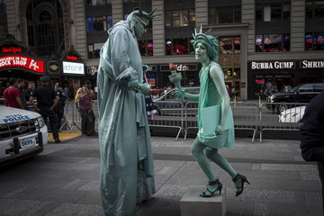 A woman dressed up as the Statue of Liberty teases and harasses a man who is also dressed up as a Statue of Liberty in the Manhattan borough of New York