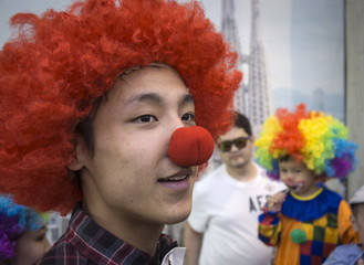 A man wearing a clown costume looks on among spectators at the Day of Clown festival in Almaty