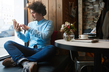 Serious businessman in cafe using digital tablet