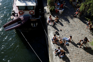 People sunbathe on the dock of the Seine river, as hot spingtime temperatures hit Paris