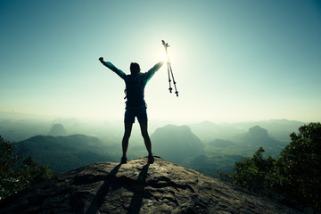 successful woman hiker open arms on sunrise mountain peak