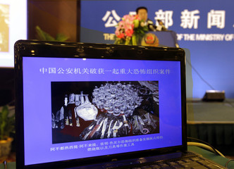 A screen displays a picture of confiscated knives and canisters during a news conference by China's Ministry of Public Security in Beijing