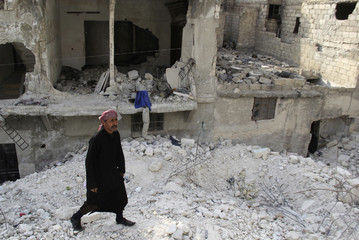 Abu Mohamed stands on debris of collapsed buildings in Aleppo's district of al-Sukari