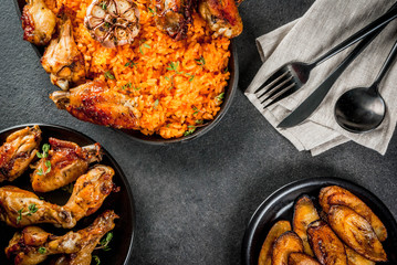 Photo Stands Ready meals West African national cuisine. Jollof rice with grilled chicken wings and fried bananas plantains.On gray stone table. Copy space top view